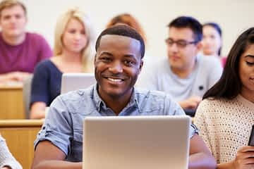 student happy at class at college since joining greek life